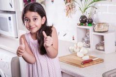 Les belles petites 7 années du Moyen-Orient de fille fonctionne avec le couteau et l'oignon dans la cuisine blanche Projectile de Images libres de droits