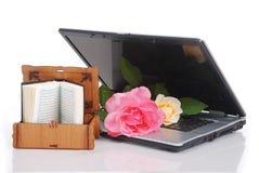 Les belles roses ordinateur portatif et le livre sacré de l'Islam ont mis t Photo stock