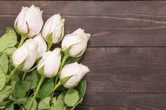 Les belles roses rose-clair sont sur le fond en bois Photos stock