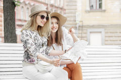 Les belles touristes de filles recherchent une adresse sur la carte se reposant sur le banc image stock