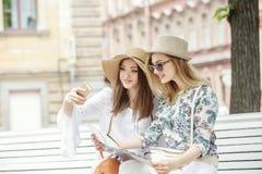 Les belles touristes de filles recherchent une adresse sur la carte se reposant sur le banc photos libres de droits
