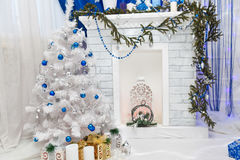 Les belles vacances ont décoré la pièce avec des présents d'arbre de Noël sous elles Photo libre de droits