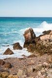 Les belles vagues de rupture contre des roches en turquoise arrosent sur le fond de l'Océan Atlantique Photo libre de droits