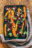 Les betteraves et les carottes cuites au four dans un vintage noircissent la casserole photographie stock libre de droits