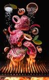 Les biftecks de boeuf crus avec des légumes et des épices volent au-dessus du feu de flambage de barbecue de gril photos stock