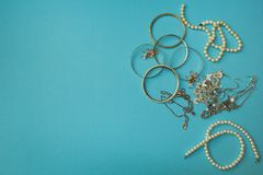 Les bijoux et toute autre substance des femmes sur un fond bleu photographie stock libre de droits