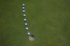 Les billes de putt de golf rayent le trou   Images libres de droits
