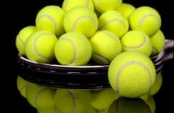 Les billes de tennis se sont rassemblées sur la raquette de tennis Image libre de droits
