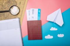 Les billets d'avion avec le passeport et le papier surfacent sur le backgroun de carte du monde Image stock
