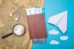 Les billets d'avion avec le passeport et le papier surfacent sur le fond de carte du monde, topview Le concept des transports aér Photos stock