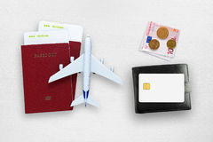 Les billets d'avion, les passeports, la carte de crédit, l'argent et le jouet surfacent photographie stock