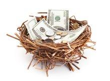 Les billets d'un dollar et les pièces dans des oiseaux nichent Photographie stock