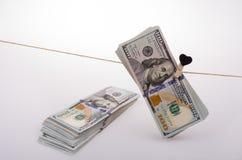 Les billets de banque du dollar avec un coeur coupent sur une ficelle Photo stock