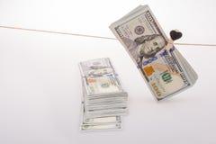 Les billets de banque du dollar avec un coeur coupent sur une ficelle Photo libre de droits