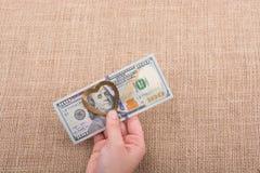 Les billets de banque du dollar avec un coeur coupent sur une ficelle Image libre de droits