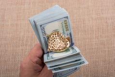 Les billets de banque du dollar avec un coeur coupent sur une ficelle Images stock
