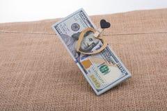 Les billets de banque du dollar avec un coeur coupent sur une ficelle Image stock