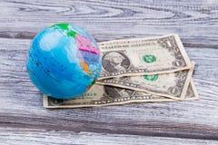 Les billets de banque et le globe des dollars des Etats-Unis sur le bureau en bois apprêtent Image libre de droits