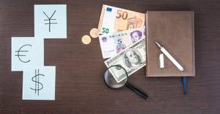 Les billets de banque internationaux, pièces de monnaie, le bloc-notes, autocollants avec la devise se connecte la table en bois  Photos stock