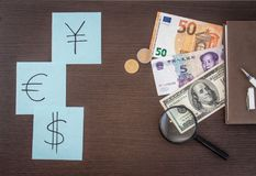 Les billets de banque internationaux, pièces de monnaie, le bloc-notes, autocollants avec la devise se connecte la table en bois  Photos libres de droits