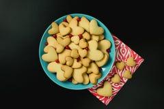 Les biscuits à un coeur forment avec la canneberge dans un plat bleu B noir Photographie stock libre de droits