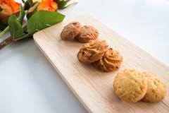 Les biscuits assortis sur le fond blanc de conseils en bois et se sont levés Photographie stock libre de droits