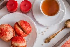 Les biscuits avec de la crème de fraise couverte de arrose o, les biscuits ronds rouges sur un plateau, tasse de thé sur un fond  Photographie stock libre de droits