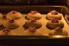 Les biscuits crus de miel avec des noix dans le four sur une plaque de cuisson avec le papier parcheminé, préparent pour la cuiss Image libre de droits