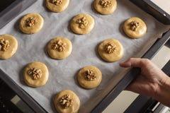 Les biscuits crus de miel avec des noix sur une plaque de cuisson avec le papier parcheminé, préparent pour la cuisson Photo stock