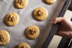 Les biscuits crus de miel avec des noix sur une plaque de cuisson avec le papier parcheminé, préparent pour la cuisson Photo libre de droits