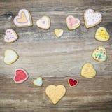 Les biscuits de coeur avec un coeur forment sur la table en bois, l'amour a de concept Photo libre de droits