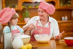 Les biscuits de cuisson de grand-mère et de petite-fille préparent la pâte Images libres de droits