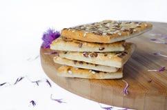 Les biscuits de grain empilés sur un conseil en bois avec le champ fleurit dos de blanc Images stock