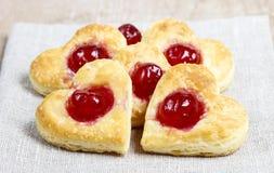Les biscuits de pâte feuilletée dans la forme de coeur ont rempli de cerises Image libre de droits