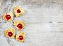 Les biscuits de pâte feuilletée dans la forme de coeur ont rempli de cerises Photos stock