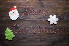 Les biscuits de pain d'épice de Noël avec le texte et le pin de ruban de Joyeux Noël s'embranchent sur le fond en bois foncé Fond Photo libre de droits