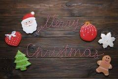 Les biscuits de pain d'épice de Noël avec le texte et le pin de ruban de Joyeux Noël s'embranchent sur le fond en bois foncé COM  Photographie stock libre de droits