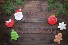Les biscuits de pain d'épice de Noël avec le texte et le pin de ruban de Joyeux Noël s'embranchent sur le fond en bois foncé COM  Photos stock