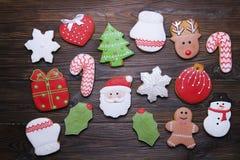 Les biscuits de pain d'épice de Noël avec le texte et le pin de ruban de Joyeux Noël s'embranchent sur le fond en bois foncé COM  Photo libre de droits