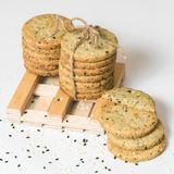 Les biscuits de sésame empilent avec la ficelle rustique d'isolement sur le fond blanc Photo carrée image libre de droits