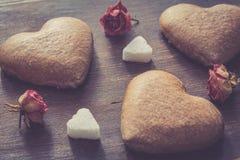 Les biscuits en forme de coeur et sèchent les fleurs roses Photographie stock