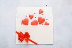 Les biscuits en forme de coeur rouges volent hors de l'enveloppe images libres de droits