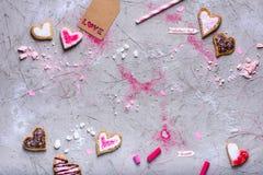 Les biscuits en forme de coeur de valentines avec amour étiquettent sur la surface grise avec l'espace de copie Photographie stock libre de droits