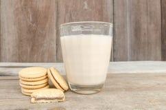 Les biscuits et le verre savoureux de lait s'étendent sur un fond en bois de table Photographie stock