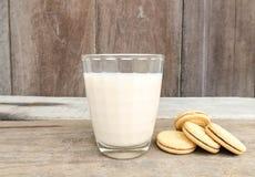 Les biscuits et le verre savoureux de lait s'étendent sur un fond en bois de table Image stock