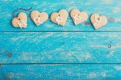Les biscuits faits maison de forme de coeur sur le fond bleu, expriment HEUREUX Image stock