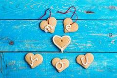 Les biscuits faits maison de forme de coeur sur le fond bleu, m'exprime l'AMOUR Y Image libre de droits