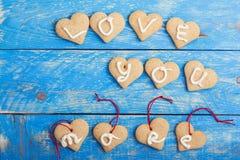 Les biscuits faits maison de forme de coeur sur le fond bleu, mots VOUS AIMENT Image stock