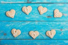Les biscuits faits maison de forme de coeur sur le fond bleu, mots VOUS AIMENT Image libre de droits