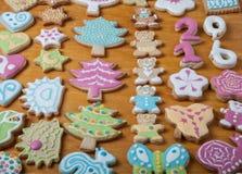 Les biscuits faits maison de pain d'épice avec le glaçage ont coloré des dessins sur le bois Photographie stock libre de droits